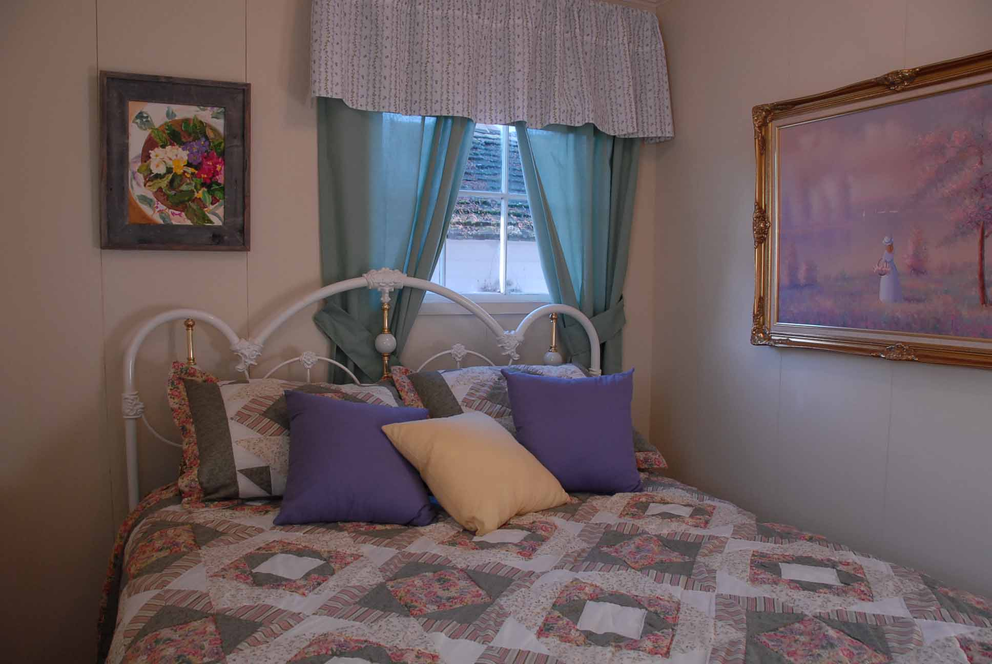 The master bedroom, includes queen size bed with white iron Victorian headboard, a picture on the wall of a girl picking flowers by a lake and a picture of flowers
